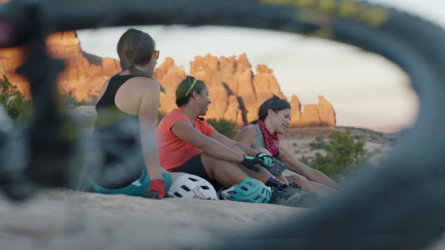 three young women sit and talk on moab bike trail overlooking scenic sandstone spires. - ruhen stock-videos und b-roll-filmmaterial