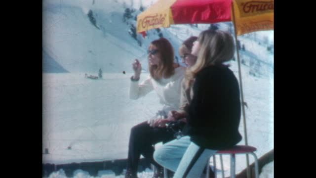 Three young women sitting beneath a red and yellow umbrella nearest the camera is Patti Boyd and in the center Cynthia Lennon / The woman on the left...