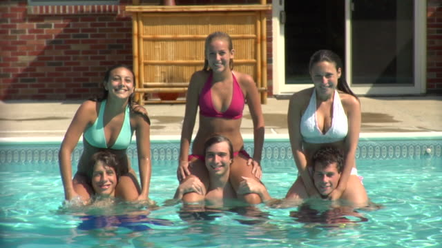 ms, three young women sitting on men's shoulders in swimming pool, portrait, middlesex, new jersey, usa - headshot stock videos & royalty-free footage