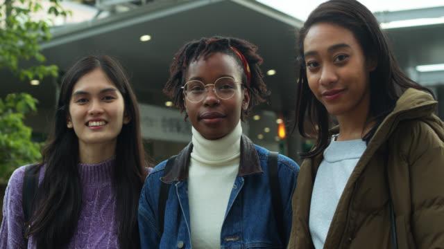 Drei junge Frauen schmundet bei der Kamera auf Straße in Tokio