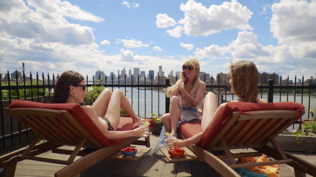 WS TD Three young women sunbathing on deck overlooking East River and Manhattan skyline / New York City, USA