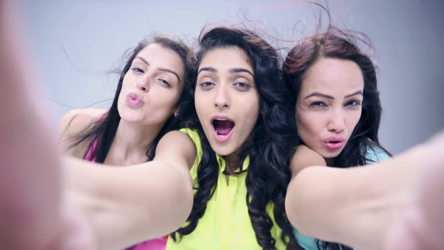 Three young women taking selfie with a mobile phone