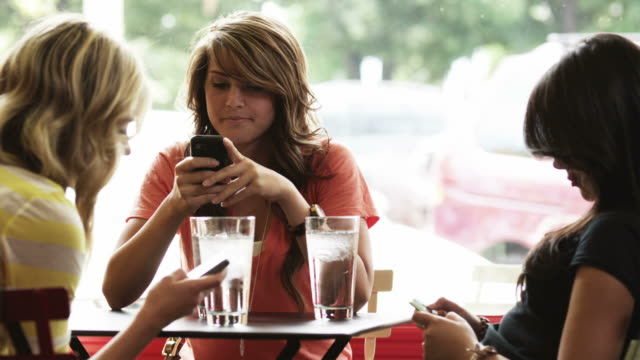 MS Three young women using mobile phones in cafe, Provo, Utah, USA