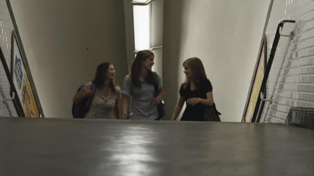 vidéos et rushes de ms three young women walking up stairs in metro station / paris, france - trois personnes