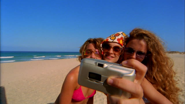 Three young women wearing sunglasses on a beach take a picture of themselves.
