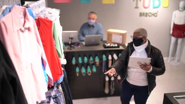 vidéos et rushes de les propriétaires du magasin d'épargne font une réunion, tous deux portant le masque facial - boutique