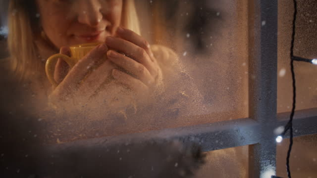 vídeos de stock e filmes b-roll de ms thrilled woman drinking a hot drink while looking at snow falling outside her window. - coffee drink