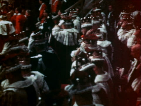 vidéos et rushes de pan throne of queen elizabeth ii to group of men putting on hats during coronation ceremony - 1953
