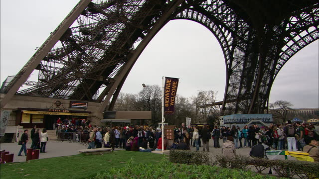 throngs of tourists gather beneath the eiffel tower. - ticket counter stock videos & royalty-free footage