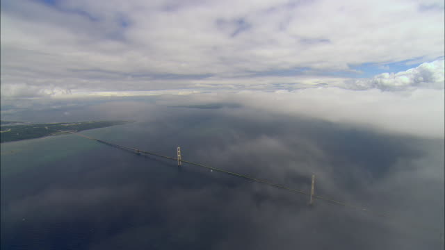 aerial through clouds to view of traffic passing over mackinac bridge/ mackinac island, michigan - hd format stock-videos und b-roll-filmmaterial