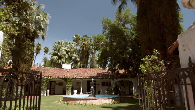 ds through entry gate of spanish colonial revival style estate with water-fountain - inn stock videos and b-roll footage