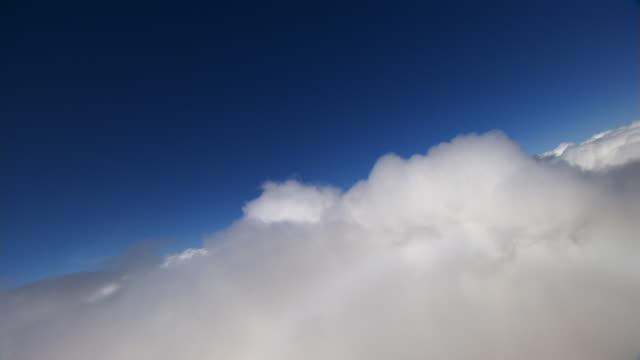 Through fluffy clouds, tilted flight
