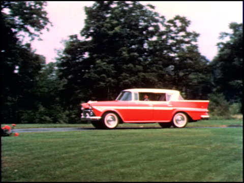 ws pov through front window of car as it drives down road through new postwwii american suburb / ws tracking shot of new 1958 amc rambler rebel... - suburban stock videos & royalty-free footage
