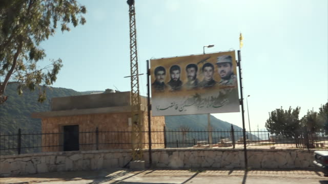 POV through hills of Hezbollah-occupied southern Lebanon with roadside tributes to fallen fighters