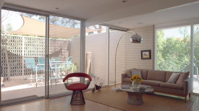 TS through interior mid-century modern cottage at Racquet Club Garden Villas with kitchen and view of garden patio