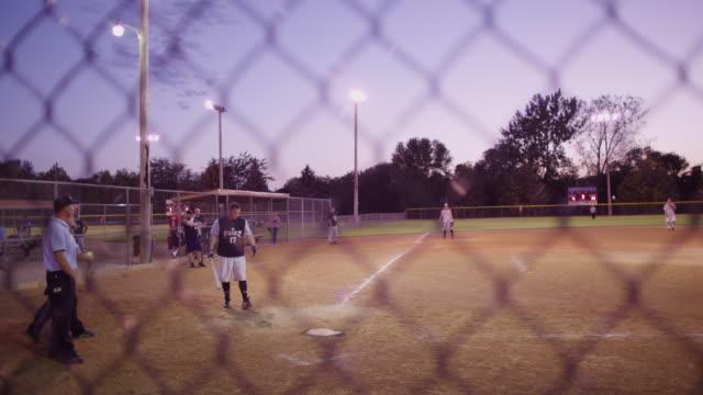 vídeos y material grabado en eventos de stock de through the chain link fence at a men's league softball game, the first pitch is a ball, the 2nd pitch is pop fly foul ball. - sófbol