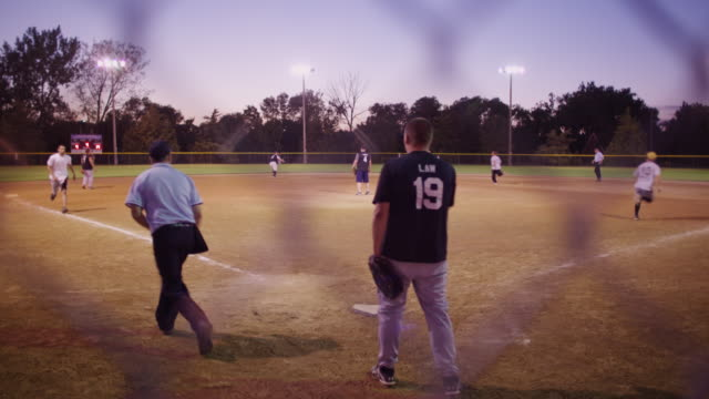 through the chain link fence behind the umpire and catcher at a men's league softball game, the batter connects, runners come home. - sports league stock videos & royalty-free footage