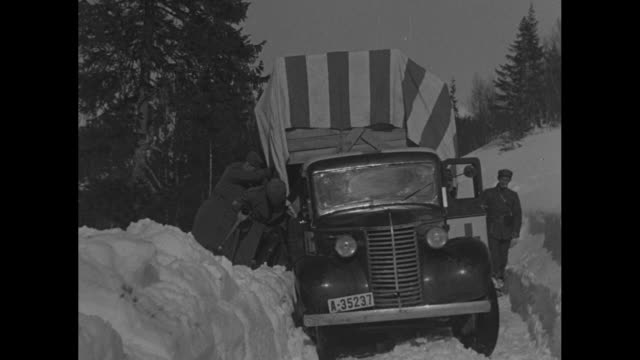 through windshield while driving through snowy norwegian countryside / tilted truck slowly moves in snow with men pushing against it while smiling... - world war ii stock videos & royalty-free footage