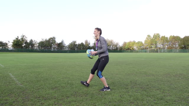 Throwing a Rugby Ball to her Coach