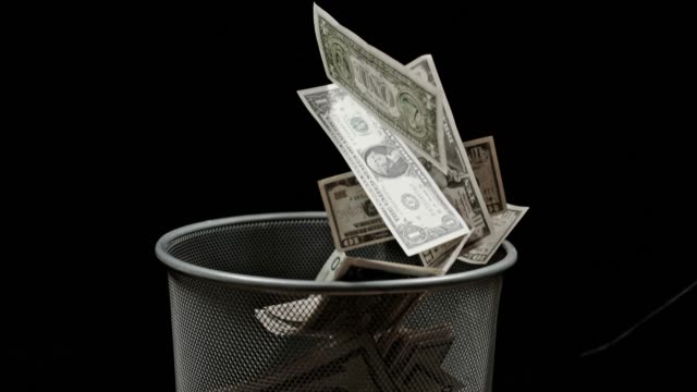 slo mo throwing american dollars bills into trash bin - loss stock videos & royalty-free footage