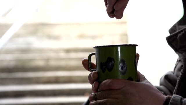 HD SUPER SLOW-MO: Throwing Coins Into Cup Of A Homeless