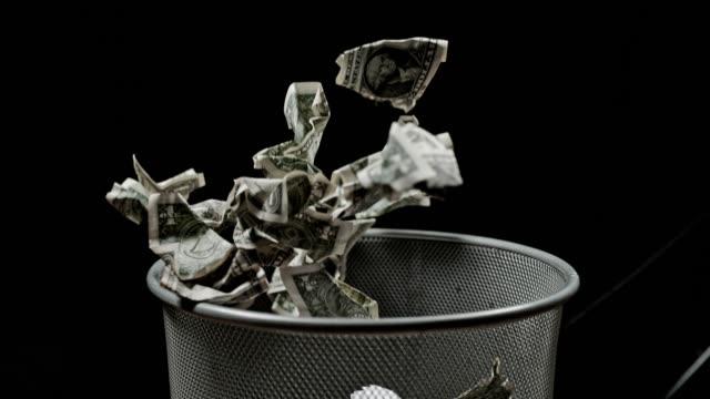 SLO MO Throwing crumpled dollars into trash