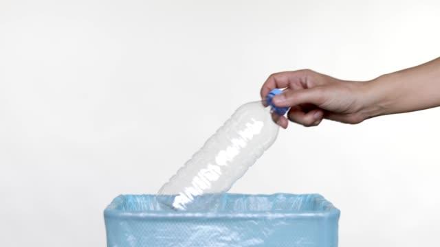 vídeos de stock, filmes e b-roll de jogando garrafa de plástico vazia na lixeira - poluição do plástico