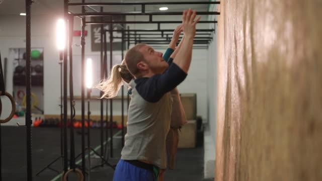 Throwing medicine ball at gym