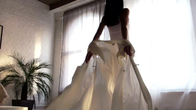lanciare apertura tende in appartamento di mattina luce li - lingerie video stock e b–roll