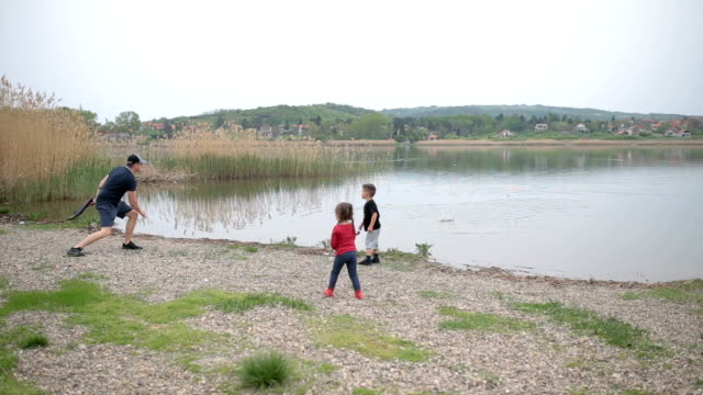 throwing rocks in the lake with father - standing water stock videos & royalty-free footage