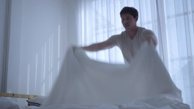throwing white blanket on bed - clean stock videos & royalty-free footage