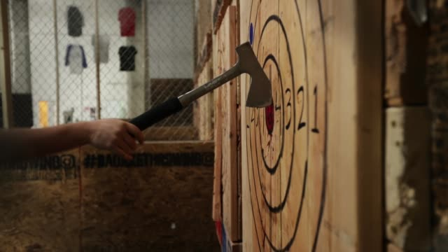 stockvideo's en b-roll-footage met thrown hatchets land in wood target walls at bad axe throwing march 28 2018 in washington dc axe throwing is growing in popularity and bad axe which... - bijl