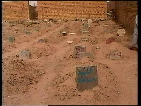 vídeos de stock, filmes e b-roll de shot thru deserted town past damaged buildings gv makeshift graveyard in former football stadium - fallujah