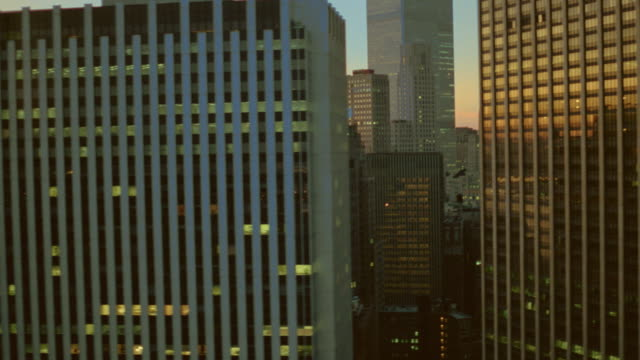 vidéos et rushes de aerial thru skyscrapers in downtown new york city at sunset along brooklyn bridge - 1990 1999