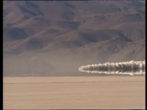 vídeos de stock e filmes b-roll de thrust ssc creates huge dust trail as it emerges from heat haze during successful land speed record attempt to break sound barrier in black rock... - nevada