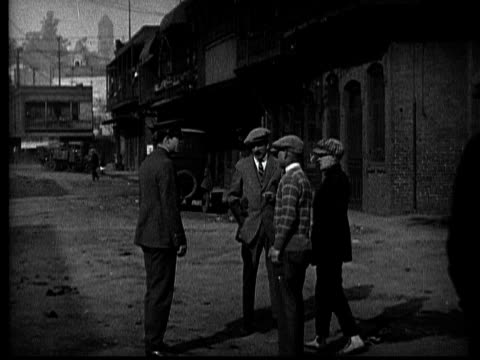 vidéos et rushes de ms, b&w, thugs attacking police officer on street, 1920's  - agression
