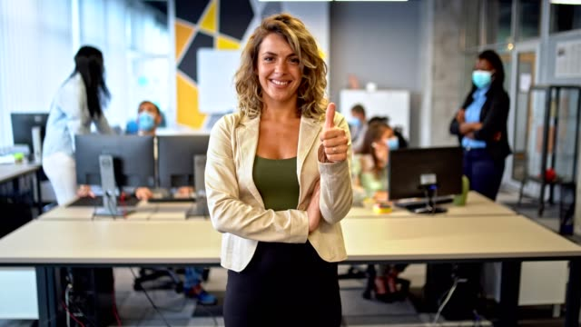 thumb up for a good work - team leader stands in her office in front of the colleagues and shows thumb up - thumbs up stock videos & royalty-free footage