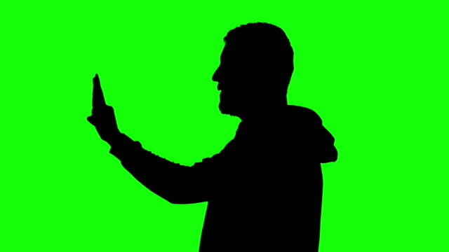 thumbs up by man silhouette in front of green screen - arms raised stock videos & royalty-free footage