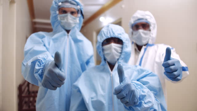 thumbs up by three doctors wearing ppe suits suggesting hope victory and determination - positive emotion stock videos & royalty-free footage