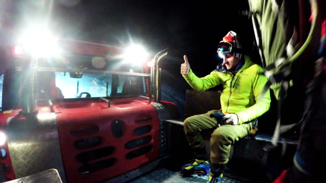 vidéos et rushes de feu vert. grimpeurs montant en bas en dameuse à neige nuit - phare de véhicule