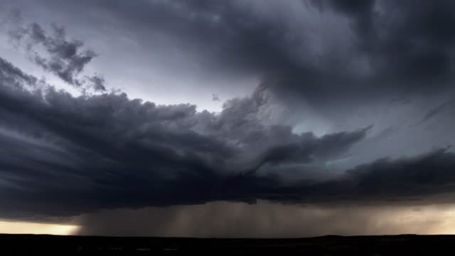 Thunderstorm with heavy rain and multiple lightning flashes hovering over dark prairie, time lapse
