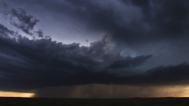 Thunderstorm with pouring rain and multiple lightning flashes over prairie, time lapse