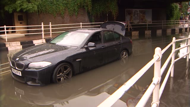 thunderstorms and flash floods across london and the south east england london battersea ext flooded underpass and people taking photographs / car... - underpass stock videos and b-roll footage