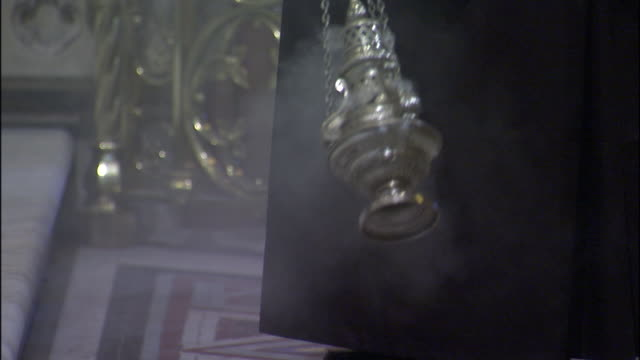 vídeos de stock e filmes b-roll de a thurible swings back and forth, dispensing incense in a church. - padre