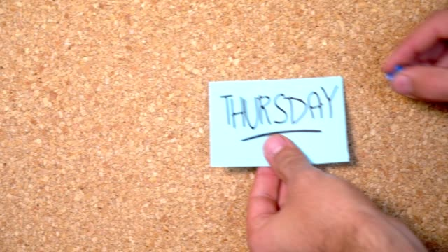 thursday word on paper pinning up on corkboard by a man - thursday stock videos and b-roll footage