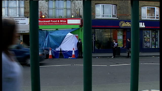 thusha kamaleswaran shooting in stockwell police search for gunman police officer outside forensics tent at scene of crime block of council flats... - ストックウェル点の映像素材/bロール