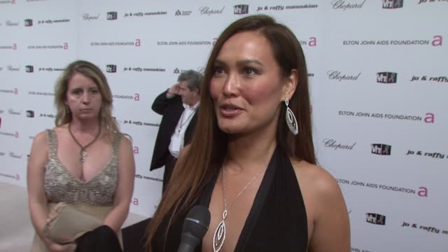 vídeos de stock, filmes e b-roll de tia carrere on attending the elton john party on the oscars and on what she's looking forward to tonight at the 17th annual elton john aids... - tia carrere