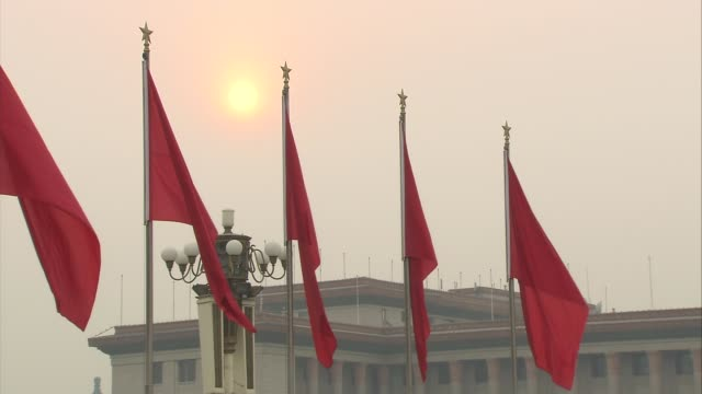 vídeos de stock, filmes e b-roll de beijing tiananmen square feature of monument near to the monument to the people's hero with golden sun visible in sky row of red flags in square... - portão da paz celestial de tiananmen