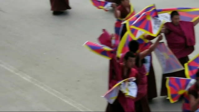 dalai lama accuses china of 'cultural genocide'; china: ghansu: xiahe: ext buddhist monks marching down main street with flag of tibet crowded... - tibet stock videos & royalty-free footage