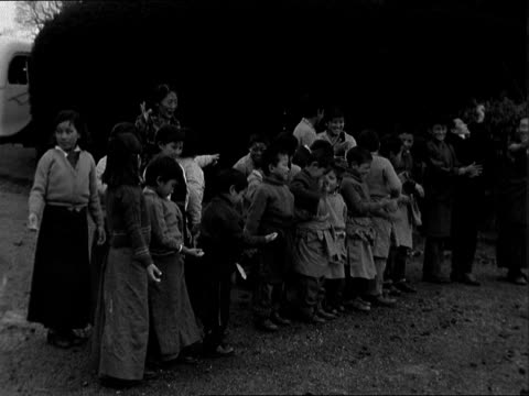 east sussex sedlescombe tibetan children along singing ms group chanting prayers bv ditto flag hoisted pan up ms receive flour ms children throw... - dessert stock videos & royalty-free footage